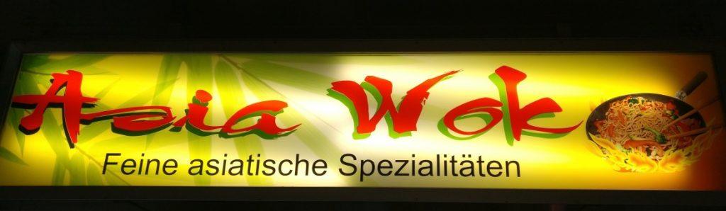 """Elektronische Mainzer Wände gibt es auch: Die Leuchtreklamen der Geschäfte prägen in unterschiedlichster Form das Erscheinungsbild der Wände in Mainz. Hier das Reklameschild des """"Asia Wok"""" am früheren Mainzer Südbahnhof, jetzt Bahnhof Römisches Theater."""