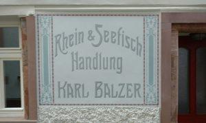 """Die """"Rhein- und Seefisch-Handling"""" von Karl Balzer gibt es schon lange nicht mehr. Wer im Internet recherchiert, findet keine Hinweise auf das frühere Unternehmen in Mainz. Als letzter Zeuge des damaligen Glanzes findet sich dieses in den Putz eingearbeitete Firmenschild. Mainzer Wände am Haus der Fischergasse 10 künden von dem Geschäft des Karl Balzer."""