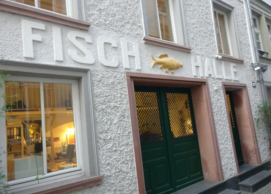 """Mainzer Wände gleich neben der Hausnummer 10 erzählen von einem weiteren historischen Ort. Die """"Fisch-Halle"""" im Haus Fischergasse Nr. 12 mit ihrem breiten Tor lässt die großen Zeiten erahnen. So klein und schmal die Mainzer Fischergasse auch ist, in den letzten Jahrhunderten spielte sich das alltägliche Leben noch nicht im Internet ab und die heutige Altstadt war Dreh- und Angelpunkt aller wirtschaftlichen Aktivitäten."""