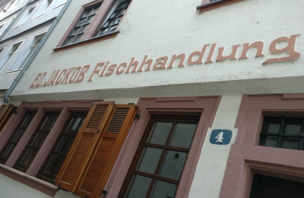 """Nur wenige Häuser weiter dokumentieren Mainzer Wände der Fischergasse 4, dass diese Gasse ihren Namen völlig zu recht trägt. Im Haus Nr. 4 fand sich früher die Fischhandlung von """"Ed. Jackob"""". Es fällt schwer, sich vorzustellen, dass in der engen Fischergasse alle Fischkäufe der Stadt Mainz getätigt wurden."""