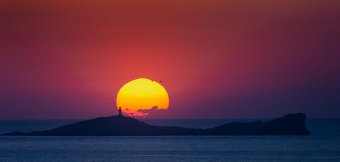 Wenn wir unser Glückshotel Ibiza buchen, dann hoffen wir auf ein Hotel nahe einem romantischen Ort wie hier an der Cala Conta mit einem Sonnenuntergang, vor dem sich die Silhouette der Insel Na Plana erhebt.