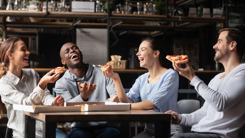 Familie und Freunde um den Tisch im Wohnzimmer versammelt, das Licht ist angenehm, im Kamin prasselt ein Feuer, es gibt leckere Speisen: All das erzeugt eine Atmosphäre der Geborgenheit  ( Foto: Shutterstock-fizkes)